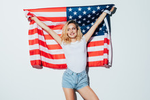 I Love America. Happy Young Woman Holding American Flag And Looking At Camera While Standing Against White Background