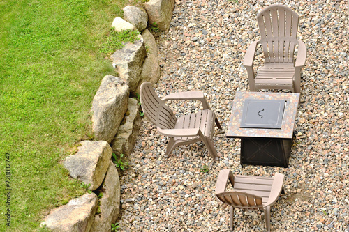 Fotografie, Obraz  Three chairs and a fire pit along a stone wall
