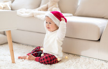 Toddler Boy Playing With A Santa Hat Around Christmas Time