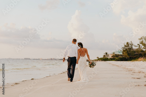Perfect Sunset Destination Beach Wedding with Beautiful Bride and Groom Walking Fototapete