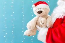 Santa Holding A Teddy Bear On A Shiny Light Blue Background