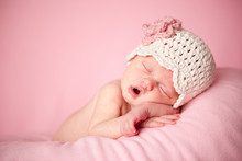 Newborn Baby Girl Sleeping In Knit Hat, Isolated On Pink