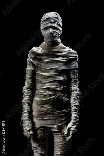 Photo Someone in peices of cloths as mummy cosplay on black background