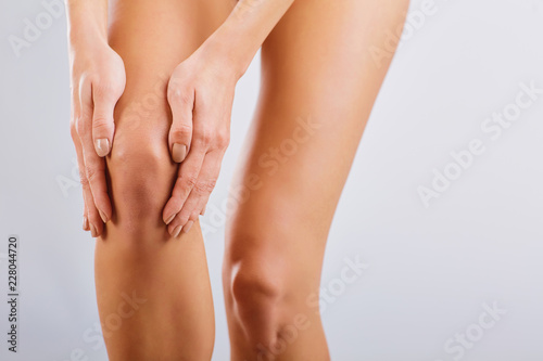 Obraz Pain, injury to the knee. A woman holds her knee with her hand. - fototapety do salonu