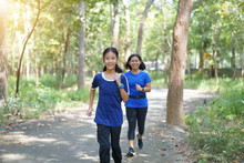Asian Mother And Daughter Jogging In A Park.