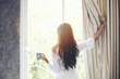 canvas print picture - Asian women drinking coffee and wake up in her bed fully rested and open the curtains in the morning to get fresh air on sunshine