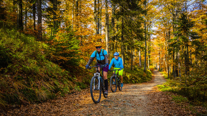Fototapeta Cycling, mountain biker couple on cycle trail in autumn forest. Mountain biking in autumn landscape forest. Man and woman cycling MTB flow uphill trail.