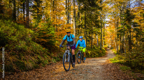 Fototapeta Cycling, mountain biker couple on cycle trail in autumn forest. Mountain biking in autumn landscape forest. Man and woman cycling MTB flow uphill trail. obraz