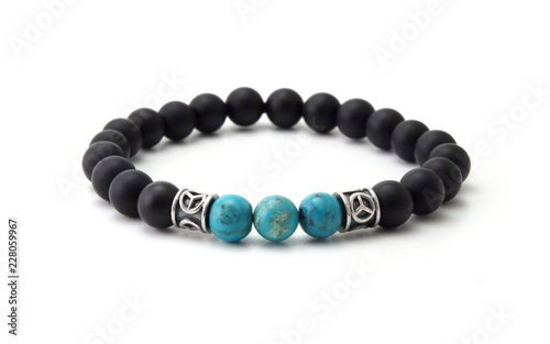 Fotografia Unpolished black onyx bracelet with turquoise beads isolated on white background