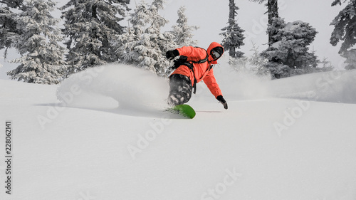 obraz dibond Man running down the mountain hill on the snowboard