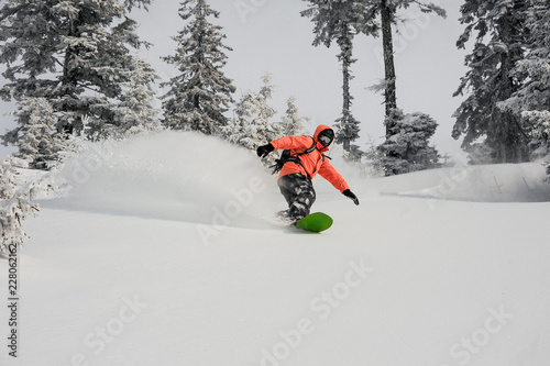 Man running down the mountain slope on the snowboard