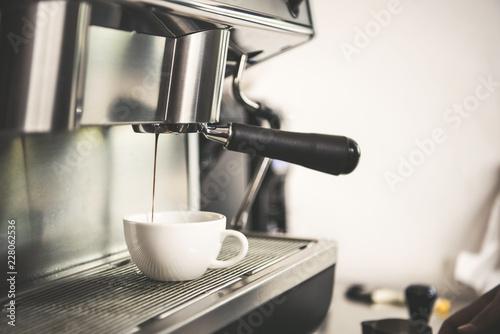 Cuadros en Lienzo Barista using coffeemaker extraction for espresso shot in cafe.