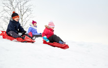 Childhood, Sledging And Season Concept - Group Of Happy Little Kids Sliding On Sleds Down Snow Hill In Winter
