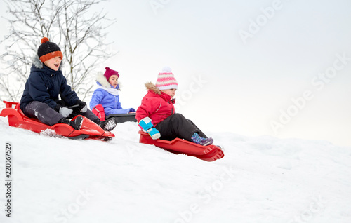 Obraz childhood, sledging and season concept - group of happy little kids sliding on sleds down snow hill in winter - fototapety do salonu