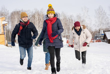 Portrait Of Four Young People Running Towards Camera Having Fun And Enjoying Nice Winter Days Outdoors, Copy Space