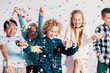 canvas print picture - Smiling multicultural group of kids having fun with confetti during friend's birthday