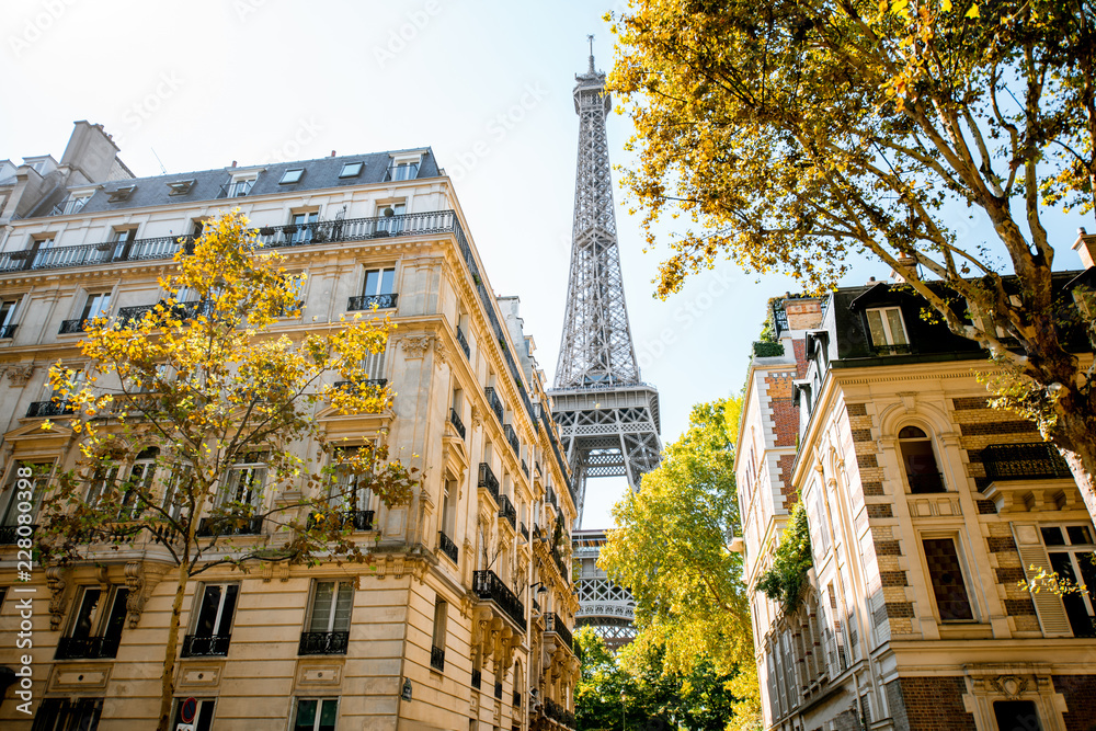 Fototapeta Beautiful street view with old residential buildings and Eiffel tower during the daylight in Paris