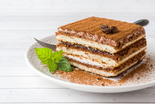 Delicious Tiramisu Cake With Coffee Beans And Fresh Mint On A Plate On A Light Background