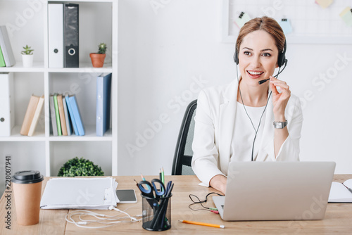 attractive professional female operator with headset and laptop in modern office Fototapeta