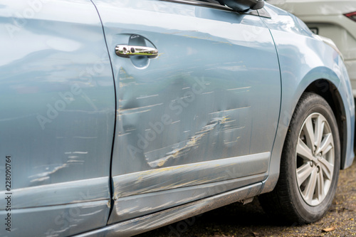 Valokuva  Car side is scratched and scraped with deep damage to the paint