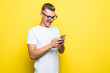 canvas print picture - Portrait of an young man in t-shirt holding mobile phone isolated over yellow background
