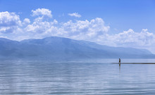 Walking On Water. A Silhouette Of A Man Walking On A Surface Of A Blue Lake, With Mountains In The Distance And Reflections In The Water.