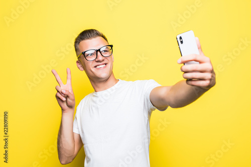 Valokuvatapetti Cheerful man looking at camera and taking selfie on yellow background
