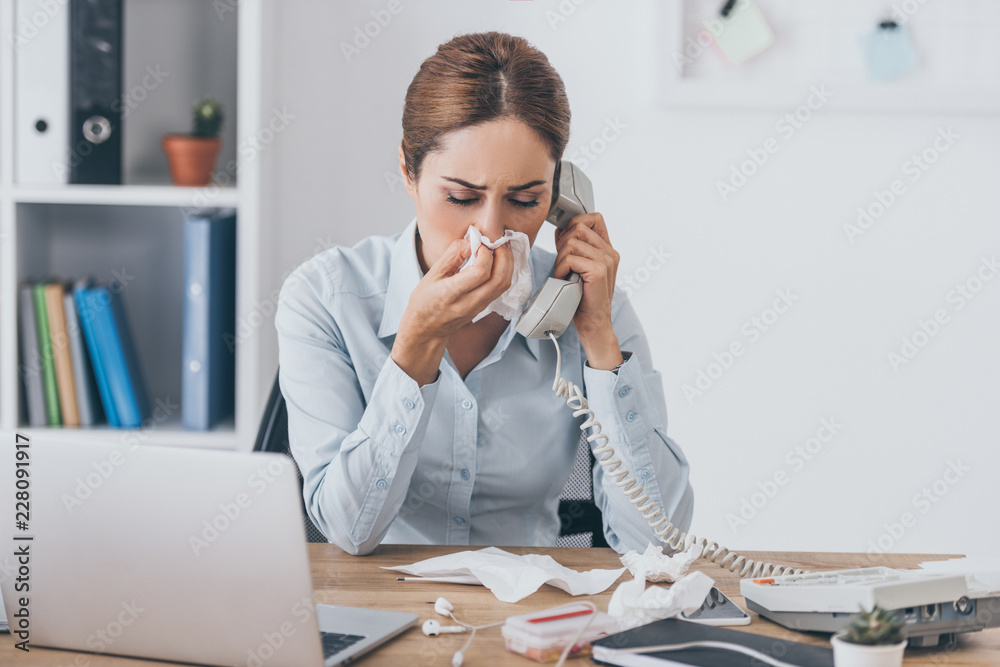 Fototapeta close-up portrait of ill adult businesswoman with runny nose talking by wired phone at office