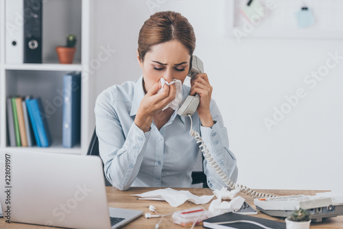 Valokuva close-up portrait of ill adult businesswoman with runny nose talking by wired ph
