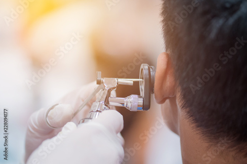 Photo ENT physician checking patient's ear using otoscope with an instrument