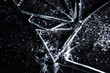 Leinwanddruck Bild - A broken glass on a dark surface, showing extreme damage, with many sharp shards. Macro close-up shot. Useful texture overlay.