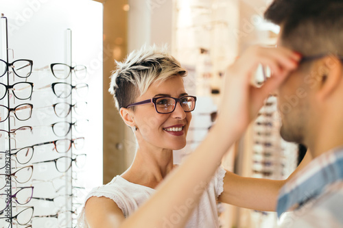 Attractive young couple in optical store buying glasses and smiling