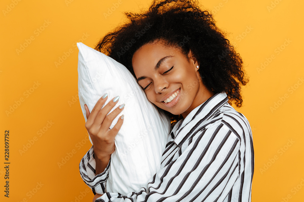 Fototapety, obrazy: Sleeping. Dreams. Woman portrait. Afro American girl in pajama is hugging a pillow and smiling, on a yellow background