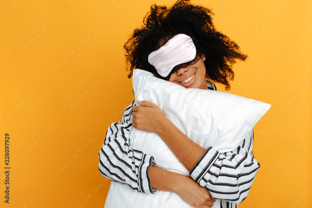 Fototapeta Sleeping. Dreams. Woman portrait. Afro American girl in pajama and sleep mask is hugging a pillow and smiling, on a yellow background