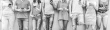 Group Of Teenager Friends Watching Smart Mobile Phones