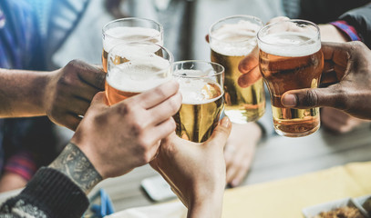 Group of friends cheering with beers in pub restaurant