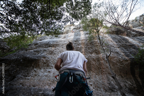 From below of anonymous man in harness looking up at mountain and checking partner climbing cliff