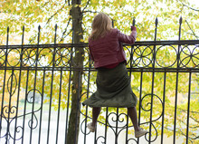 Woman Climbs Onto An Iron Fenc...