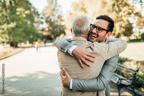 Fotografie, Tablou Family reunion. Father and son hugging outdoors.