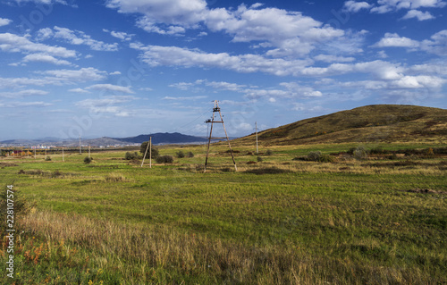 Deurstickers Texas Autumn steppe landscape. Landscape in Kazakhstan. Kazakh steppe. Power line. Yellow hills. Green grass. Blue sky with white clouds
