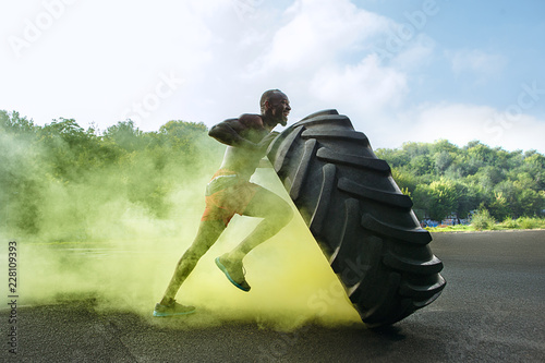 Leinwand Poster Handsome african american muscular man flipping burning big tire outdoor with sm