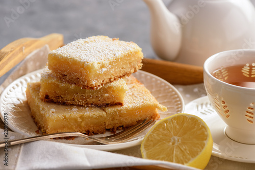 Homemade baked lemon bars and cup of tea.