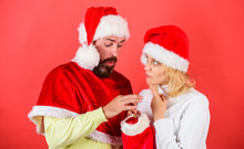 Woman And Bearded Man In Santa Hat Expecting Gift Red Background. Check Contents Of Christmas Stocking Gift Received. Christmas Gift Concept. Couple Cheerful Face Check Out Gift In Christmas Sock