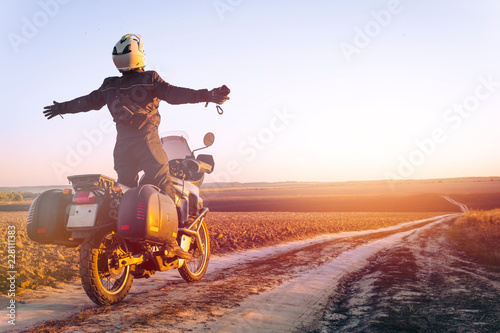 Fotografia Motorbiker travelling, autumn day, motorcycle off road, the driver stands with o