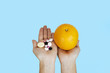 the hands of the girl on which are pills and an orange full of vitamin on a blue background