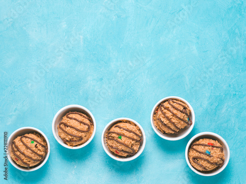 Fotografie, Obraz  Safe-to-eat raw monster cookie dough in small portion bowl on blue background