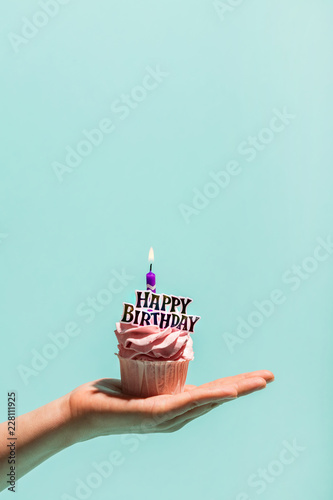 Photo  Woman's hand holding birthday cupcake with candle.