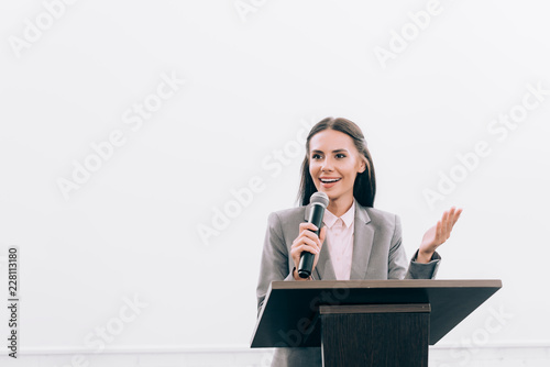 Valokuva attractive smiling lecturer talking into microphone and gesturing at podium trib