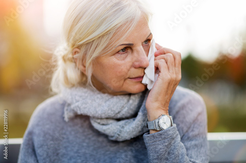 Fotografia  Weeping old woman wipes her eyes with tissue