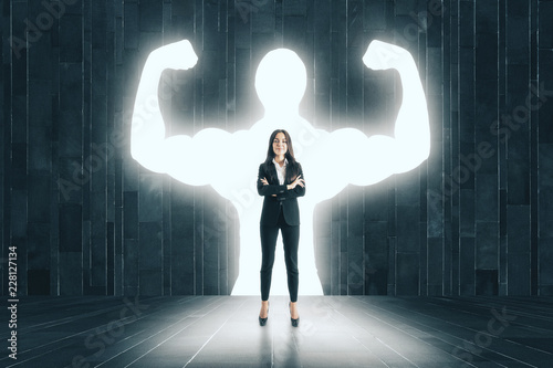 Fotografiet  Businesswoman with muscly arms